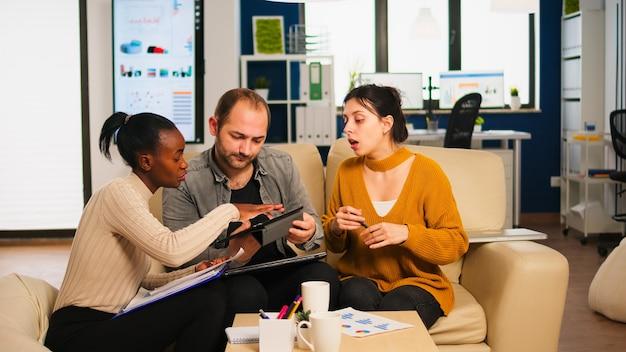 Diverse zakenmensen analyseren financieel project tijdens zakelijke bijeenkomst. multi-etnische werknemers groep luisteren collega die ideeën deelt die nieuw marketingplan bespreken dat gegevens van tablet vergelijkt.