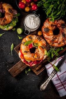 Diverse zelfgemaakte bagelsandwiches met sesam- en maanzaad, roomkaas, ham, radijs, rucola, kerstomaatjes, komkommers, met ingrediënten op een donkere betonnen ondergrond