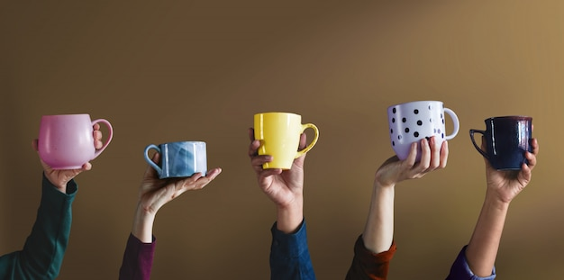 Diversiteit en levensstijl concept. mensen staken hand op om hun eigen beker en eigen favoriete drankjes te tonen