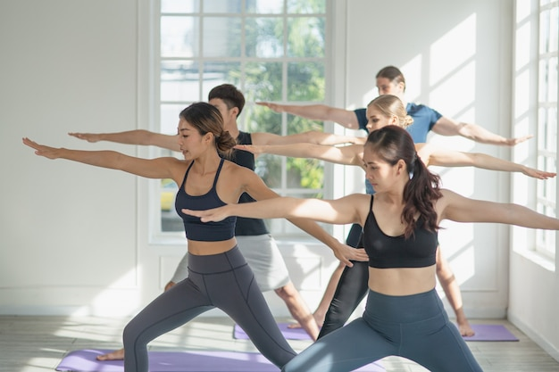 Diversiteit groep mensen en vriend strekken zich uit voor oefenyoga en training samen mediteren