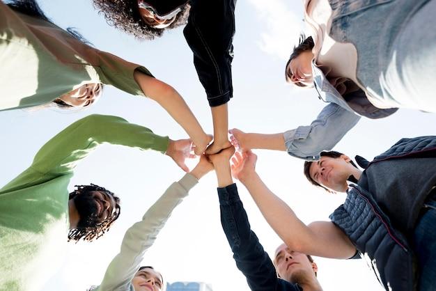 Diversiteit van mensen hand in hand onderaanzicht