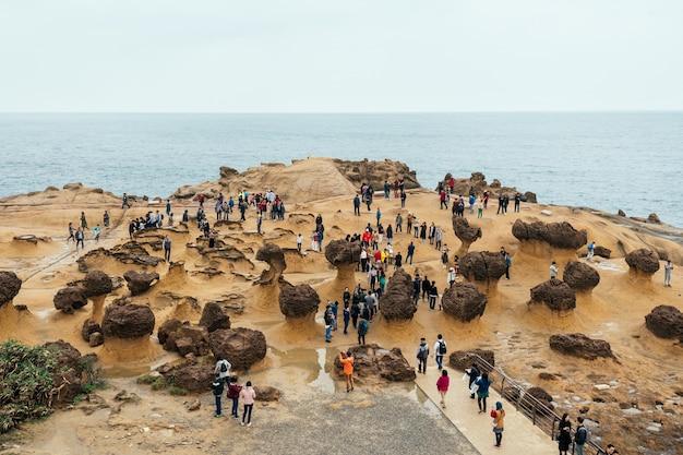 Diversiteit van toeristen die in yehliu geopark lopen, een kaap aan de noordkust van taiwan.