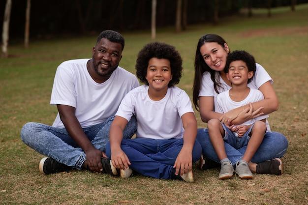 Diversiteitsgezin met afro-vader en japanse moeder. mooie gelukkige familie in het park