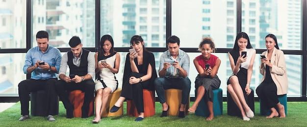 Diversiteitsmensen groep multi-etnische businessperson in toevallig kostuum die slimme telefoon met behulp van