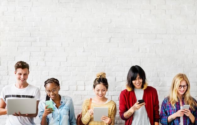 Diversiteitsstudentenvrienden die digitaal apparatenconcept gebruiken