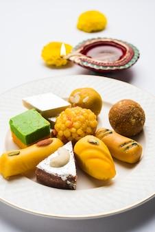 Diwali diya, snoep of mithai en geschenkdozen gerangschikt op decoratieve achtergrond. selectieve focus