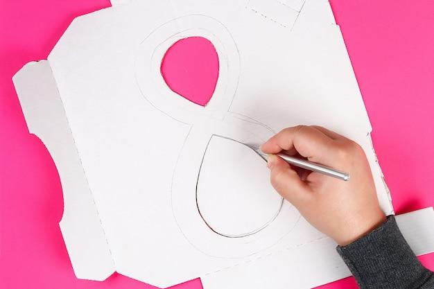 Diy acht gemaakte karton verfraaide kunstbloem gemaakte blauwe papieren zakdoekje servet roze achtergrond.
