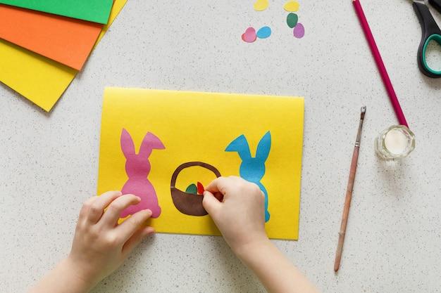 Diy-ansichtkaart stap voor stap. kaart vrolijk pasen met kinderhanden. ambachten concept voor kinderen. stap 7. lijm het konijn, het konijn, de eieren, de mand op het karton.