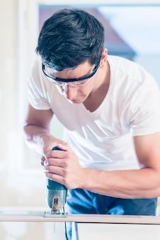 Diy-arbeider die houten paneel met malzaag snijden