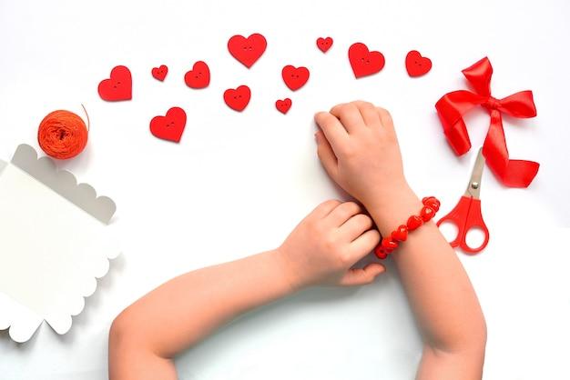 Diy armband van rode harten van kralen handgemaakt voor een meisje op een hand voor valentijnsdag.