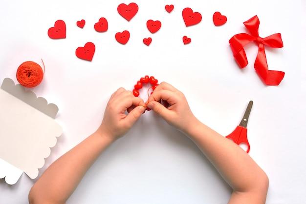 Diy babypennen geknoopte armband van rode kralen hartjes voor valentijnsdag. handgemaakte babydecoratie. handwerk concept.