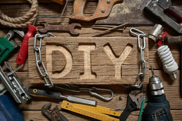 Diy-brieven op een houten raad op de achtergrond van werkende hulpmiddelen