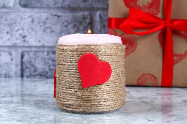 Diy decor op 14 februari. een cadeau en een kaars voor doe-het-zelf-valentijnsdag.