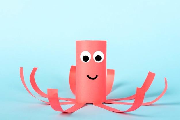 Diy en kinderen creativiteit. milieuvriendelijk hergebruik recyclen van toiletrolbuis. kinderen paper craft rode octopus met tentakels.