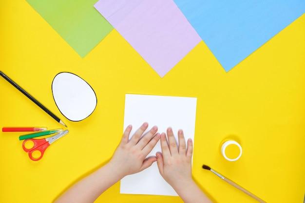 Diy en kinderen creativiteit. stap voor stap instructie maak een paaskaart met kuiken. handgemaakt paasambacht voor kinderen. bovenaanzicht