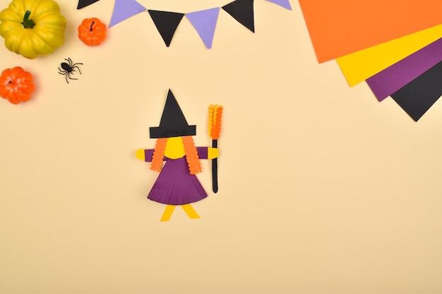Diy-halloween. we maken een heks van gekleurd papier. stapsgewijze instructies. stap 10: lijm de bezem op de heks.