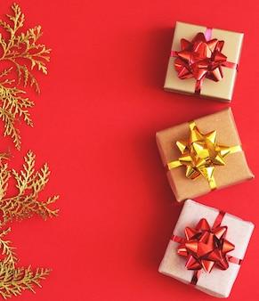 Diy handgemaakte kerstgeschenkdozen van knutselpapier. dozen en gouden takjes op een rode achtergrond. kopieer spase