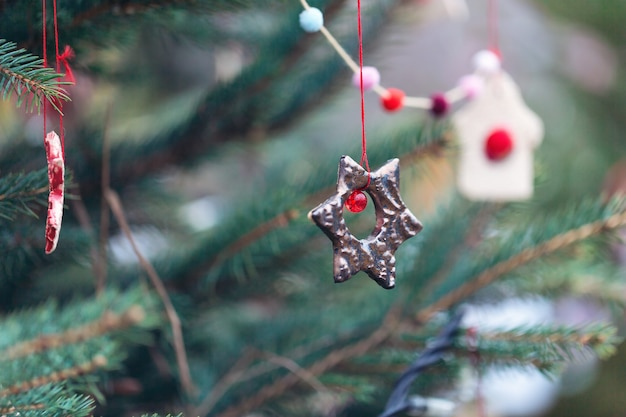 Diy-handgemaakte kleidecoratie op een kerstboom buiten. selectieve aandacht, kopie ruimte.
