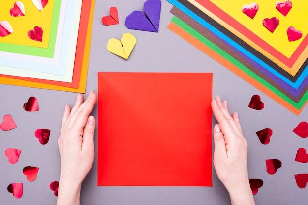 Diy-instructie. stap voor stap handleiding. het proces van het maken van een papieren hart met vleugels voor valentijnsdag.