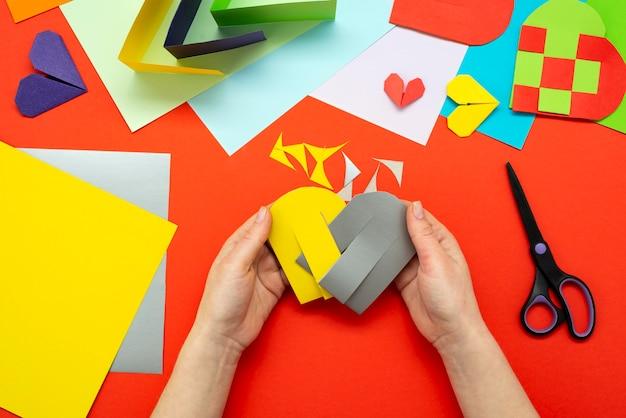 Diy-instructie. stap voor stap handleiding. het proces van het maken van een papieren hart van geel en grijs gekleurd papier voor valentijnsdag.