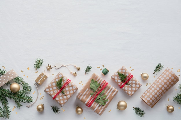 Diy kerstcadeaus in knutselpapier, handgemaakte decoraties. plat lag op wit zacht textiel tafelkleed.