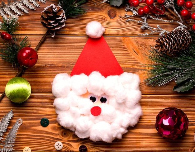 Diy kerstkaart stap voor stap. van gekleurd papier en watten op een houten tafel. vierde stap