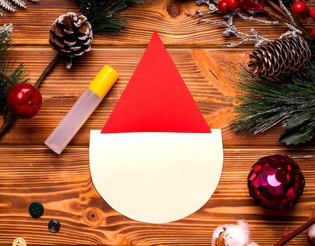 Diy kerstkaart stap voor stap. van gekleurd papier en watten op een houten tafel.