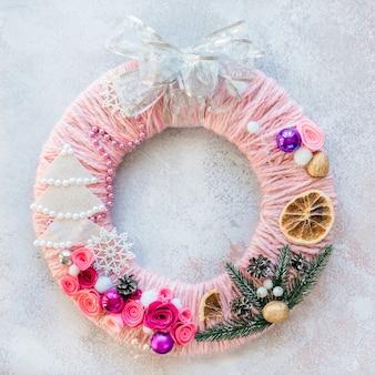 Diy kerstkrans gemaakt van vilt, wolgaren, gedroogde sinaasappels en kerstversieringen, kerst- en nieuwjaarsknutselideeën voor kinderen