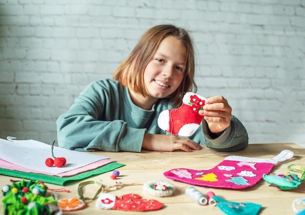 Diy kerstsok, meisje met handgemaakte vilten kerstsok