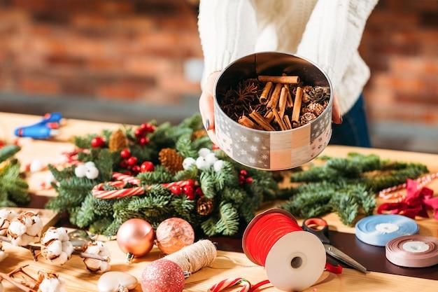 Diy kerstversiering. vrouwelijke bloemist bedrijf doos met dennenappels, kaneelstokjes en steranijs.