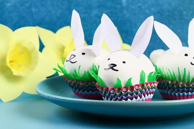 Diy konijn van paaseieren op blauwe achtergrond. geschenkideeën, decor pasen, lente. handgemaakt.