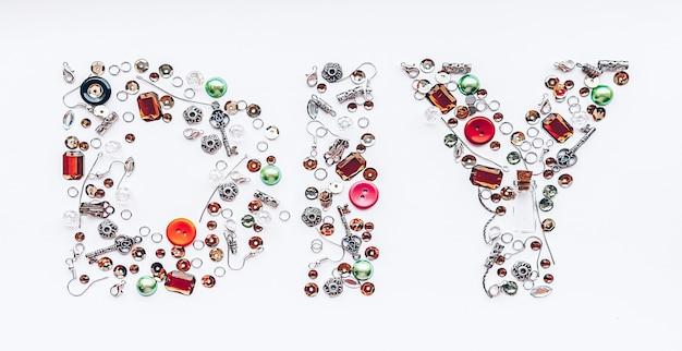 Diy-letters verzameld van handgemaakte gereedschappen zoals knopen, oordopjes, sloten, pailletten, hangers aan een