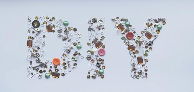 Diy-letters verzameld van handgemaakte gereedschappen zoals knopen, oordopjes, sloten, pailletten, hangers op een witte achtergrond. ambacht en hobby concept. bannerformaat.