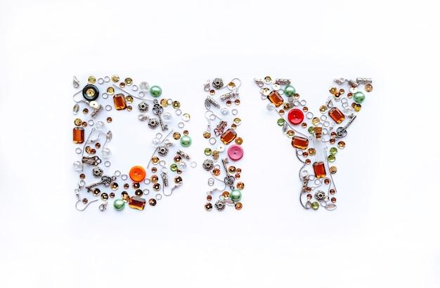 Diy-letters verzameld van handgemaakte gereedschappen zoals knopen, oordopjes, sloten, pailletten, hangers op een witte achtergrond. ambacht en hobby concept.