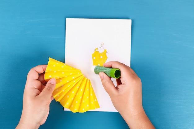 Diy moeders dag wenskaart met een papieren servet jurk en bloem decoratie.