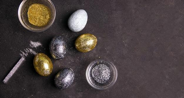 Diy pasen. eieren versierd met glitters op een donkere achtergrond. kopieer ruimte