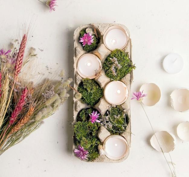 Diy pasen. kandelaar van een eierschaal op een witte achtergrond met bloemen.