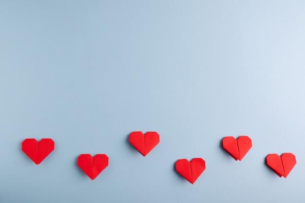 Diy rode origami harten op een blauwe tafel