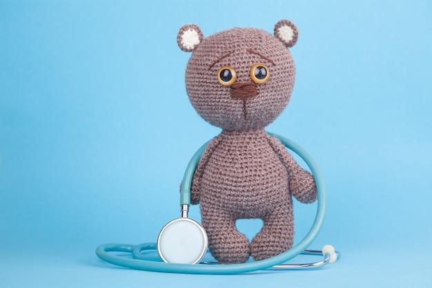 Diy speelgoed. gebreide bruine beerwelp met een stethoscoop, preventie van kinderziekten
