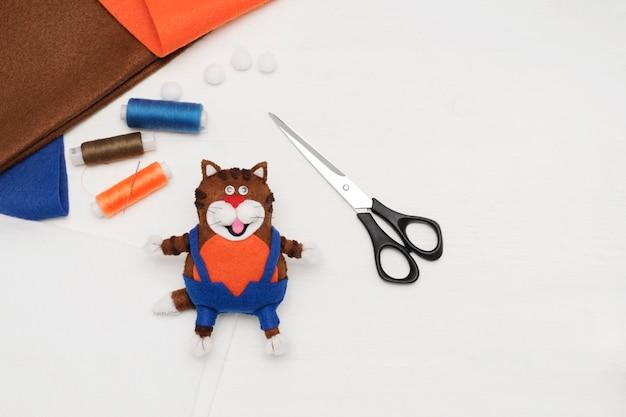 Diy. vilt, draad, schaar, speelgoedkat genaaid van vilt. het concept van naaien ambacht. bovenaanzicht
