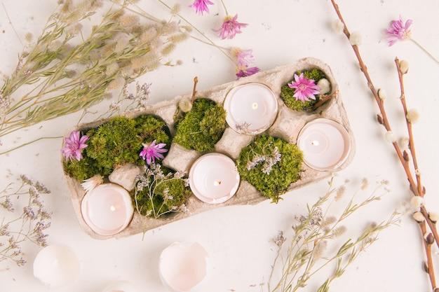 Diy voor pasen. schaal van eieren met kaarsen op een witte achtergrond met veldbloemen