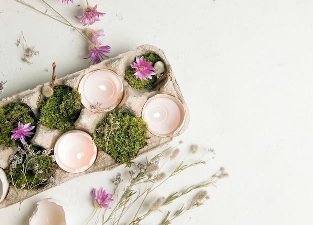 Diy voor pasen. schelpen van eieren met kaarsen op een witte achtergrond met veldbloemen.