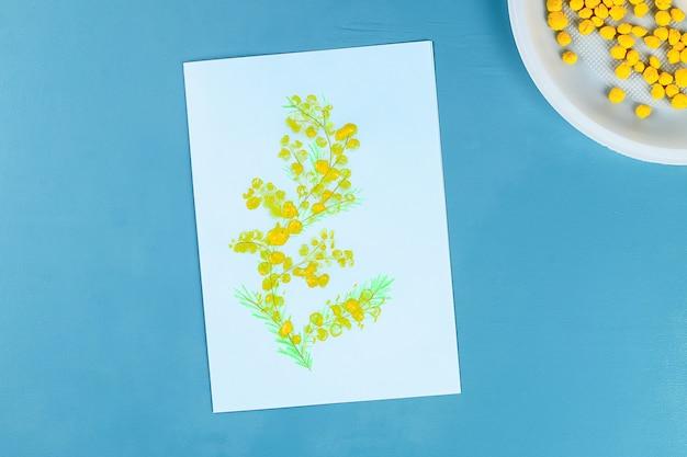 Diy wenskaart met mimosa bloemen papier ballen voor 8 maart op blauwe achtergrond.