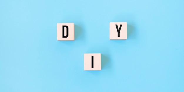 Diy-woord op houten blokken met blauwe achtergrond