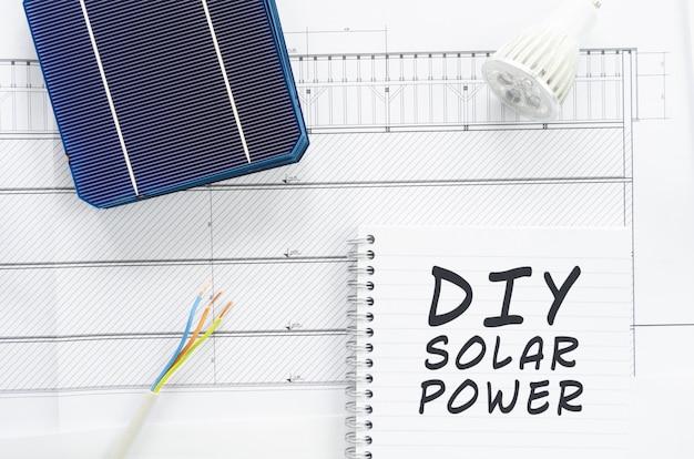 Diy zonne-energie geschreven op een notitieblok in een conceptueel beeld van doe-het-zelf thuis zonne-energiesysteem installeren met, kabels, led-lamp en zonnecellen