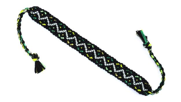 Diy zwarte geweven vriendschapsarmband met geometrisch patroon dat op witte achtergrond wordt geïsoleerd