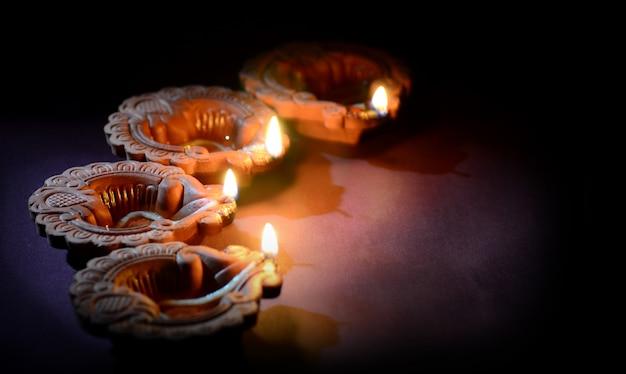 Diya-lampen van klei die tijdens diwaliviering worden aangestoken. wenskaart indian hindu light festival genaamd diwali