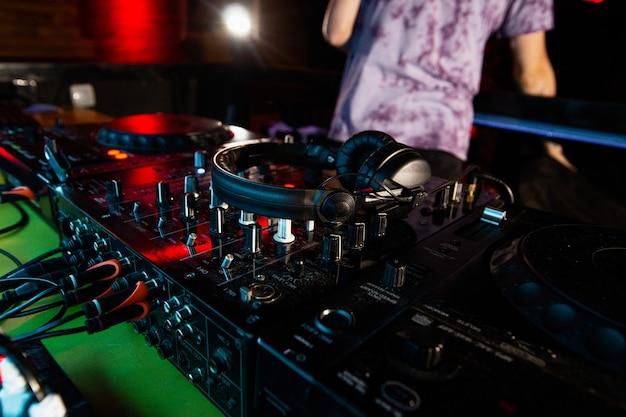 Dj beëindigt dienst. baan in nachtclub. close-up foto van schijfjockey console of draaitafels met koptelefoon erop.