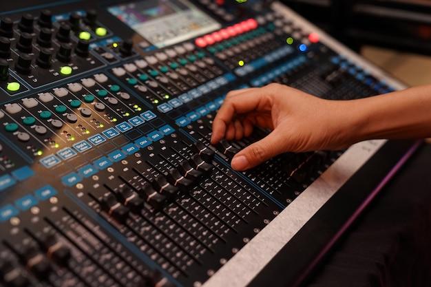 Dj bestuurt de geluidscontroller en speelt gemixte edm-muziek in de concertnachtclub op een feestje.