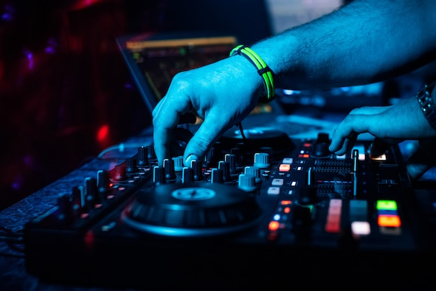 Dj combineert elektronische muziek op een professionele controller in een nachtclub